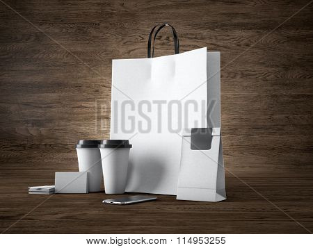 Set of white craft shopping bag, two coffee cups, business cards. Wood background. 3d render