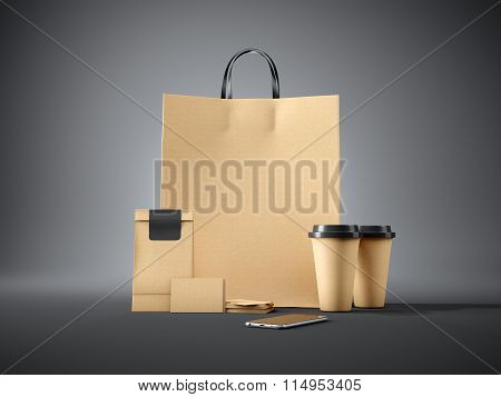 Set of brown pocket bag, two coffee cups, business cards and generic design smartphone. Black backgr