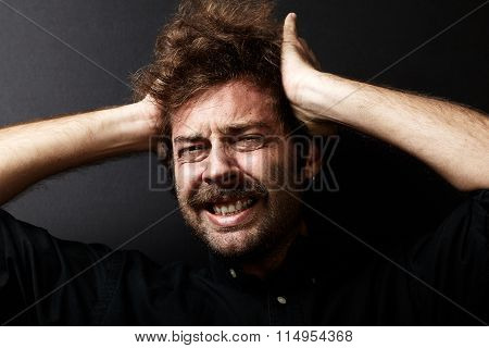 Portrait of young man who clutching his head in pain