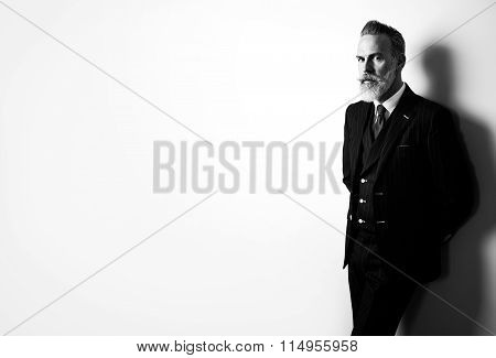 BW portrait of bearded businessman wearing trendy suit and stands against the empty white wall. Wide
