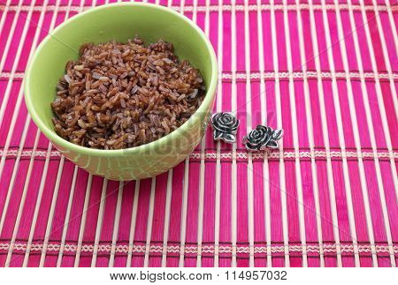 Brown rice in a bowl with metal roses on pink bamboo mat/pad