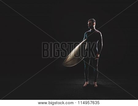 Surfer with surf board on black background