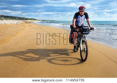 Man Goes  Sandy Beach On Mountain Bike.