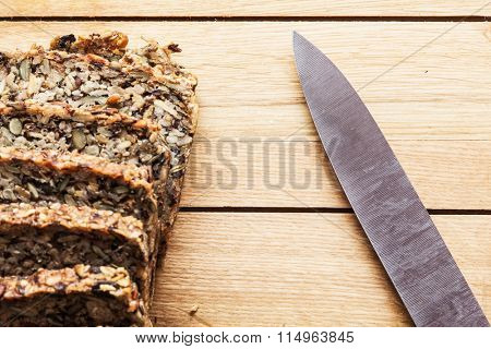 Knife and wholemeal, wholewheat bread on wooden table. Organic, healthy food, breakfast.