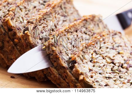 Knife in wholemeal, wholewheat bread on wooden table. Organic, healthy food, breakfast.