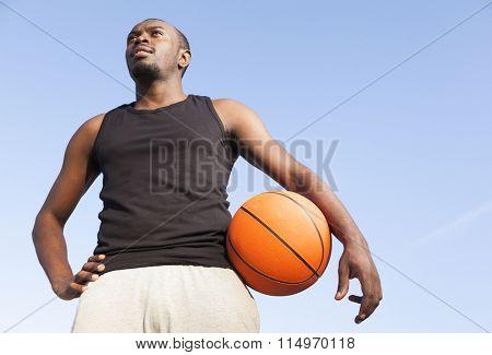 Afroamerican man street basket player holding a basketball against blue sky