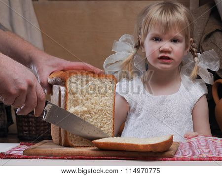 The child looks like sliced bread. On the table freshly baked bread