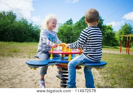 Boy And Girl Swinging On A Swing