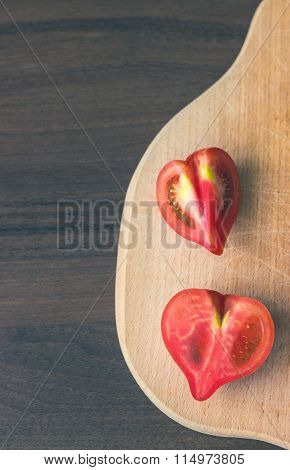Heart Shaped Tomatos On Wooden Cutting Board