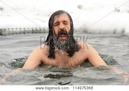 Orel, Russia - January 19, 2016: Russian Epiphany Feast. Man With Long Hair Dipping In Ice-hole