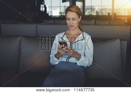 Female writing text message on her cell telephone while relaxing in coffee shop after work day
