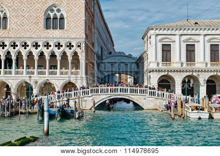 VENICE - AUGUST 27: Bridge of Sighs from the Giudecca Canal showing the hordes of tourists lining the bridge over the side canal with the Doges Palace on the left. August 27, 2015 in Venice
