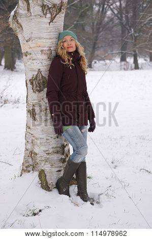 woman leaning against tree in winter
