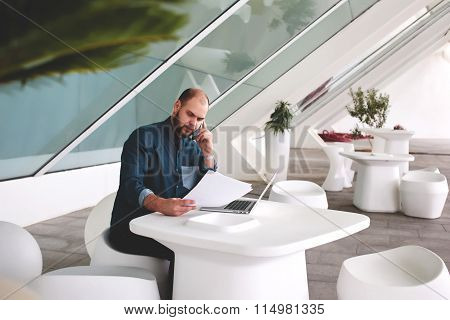 Male entrepreneur talking on mobile phone during reviewing resume