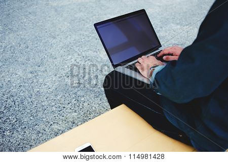 Young male chatting on laptop computer while sitting in modern interior