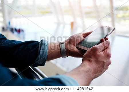 Cropped shot view of a man's hands holding cell telephone while standing in shopping center