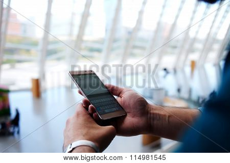Cropped shot view of man's hands orders electronic ticket via mobile phone application