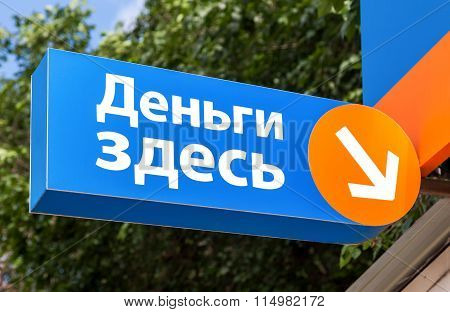 A Sign On The Facade Of The Microfinance Organisation. Text In Russian: Money Here