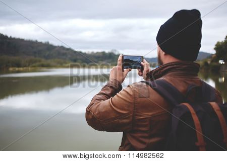 Male traveler shoots video on cell telephone of mountains and lake during journey
