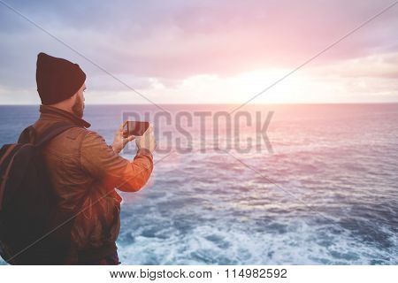Hipster guy with trendy look shoots video with ocean landscape on mobile phone