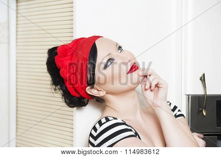 Fashion photo of sexy young brunet pin-up girl with beautiful eyes and full red lips wearing in the