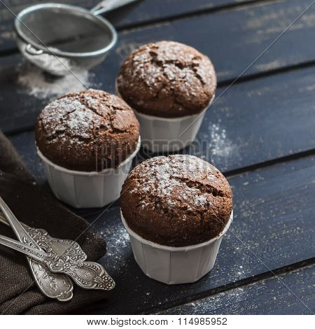 Delicious Vegan Chocolate Muffins With Icing Sugar On Dark Wooden Surface