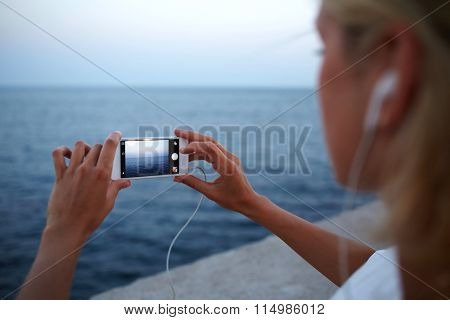 Cropped image of female tourist making photo of amazing sea view on cell telephone
