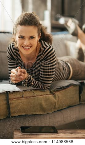 Smiling Brown-haired Stylish Woman Is Laying Down On Sofa