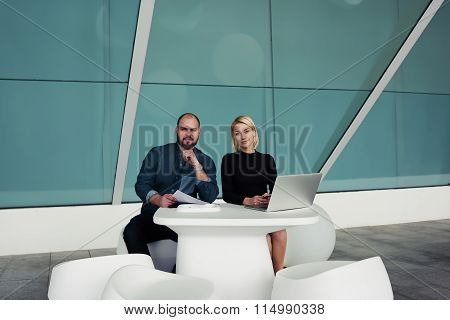 Team of professional leaders looking at camera while sitting with laptop computer in modern office