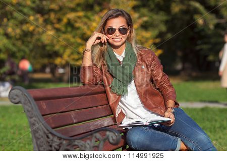 Beautiful young blond woman sitting on a bench in a park reading a book