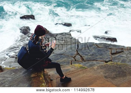 Young stylish female watching photos on cell telephone while sitting on a rock near ocean