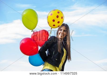 smiling young ordinary  woman in blue jeans and leather jacket  with balloons outdoors against sky