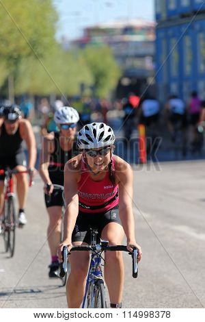STOCKHOLM - AUG 23 2015: Smiling cycling woman wearing pink tank-top followed by de-focused competitors at ITU World Triathlon event in Stockholm 2015