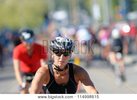 Close-up Of Cycling Woman Followed By De-focused Competitors