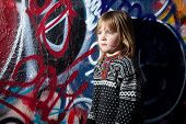 stock photo of deprivation  - child in front of graffiti wall in urban area - JPG