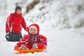 pic of snow-slide  - girl on sleigh on road and her mother in background - JPG