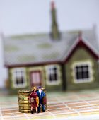 stock photo of eviction  - A couple who have just been evicted from there house carrying suitcases and walking past a pile of gold coins representing the outstanding debt they still have - JPG