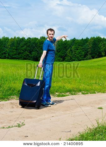 The Young Man On Road In The Field With A Suitcase