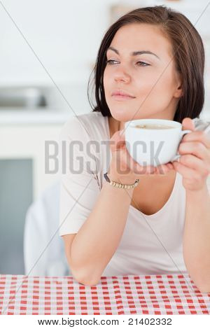 Portrait Of A Smiling Dark-haired Woman Having A Coffee