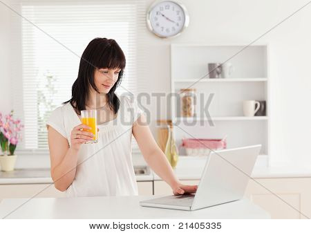 Beautiful Brunette Woman Holding A Glass Of Orange Juice While Relaxing With Her Laptop