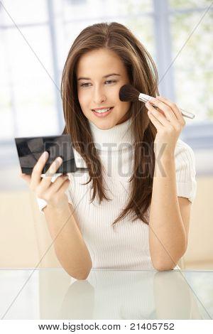 Porträt von pretty Woman mit Make-up, Spiegel und Puder Pinsel halten lächelnd.?