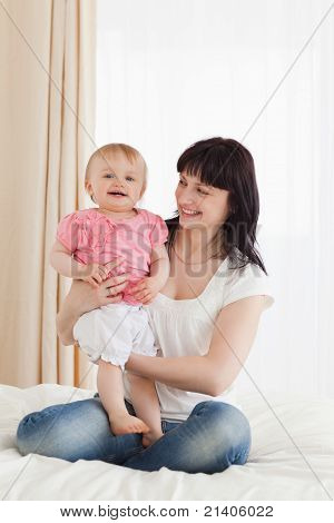 Cute Brunette Woman Holding Her Baby On Her Knees While Sitting On A Bed
