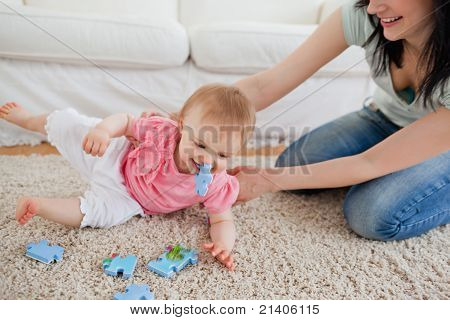 Lovely Woman And Her Baby Playing With Puzzle Pieces While Sitting On A Carpet