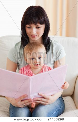 Attractive Woman Holding Her Baby And A Book In Her Arms While Sitting On A Sofa