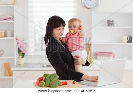 Beautiful Brunette Woman In Suit Holding Her Baby In Her Arms While Working With Her Laptop