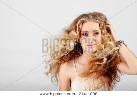 beautiful strawberry blond teenage girl with green eyes and long curly hair blowing in wind over grey studio background with copy space