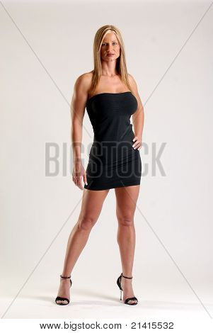 Tiny black dress on a tone blond hair woman wearing stilettos.