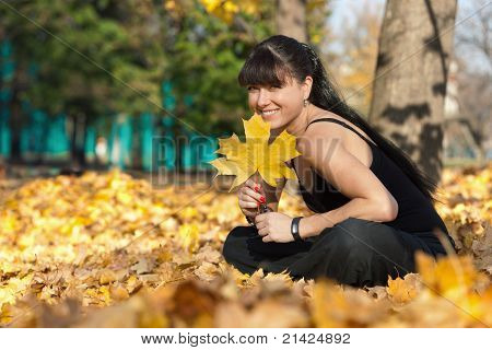 Girl In Woods Smiling and Holding Maple Leaf