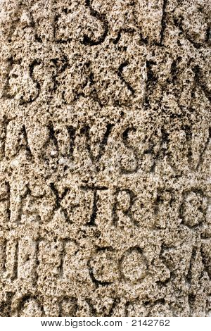Background Texture Using Fragment Of The Antique Text On A Stone Wall.