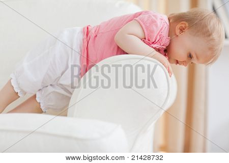 Cute blond baby standing on a sofa in the living room